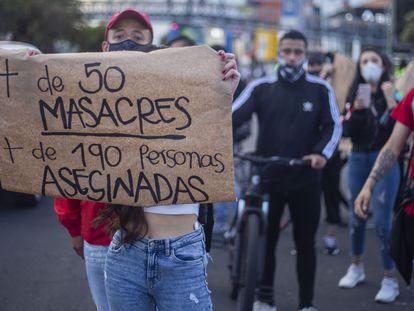 Uma mulher exibe um cartaz contra as chacinas de civis na Colômbia, durante uma manifestação em Bogotá em meados de setembro.