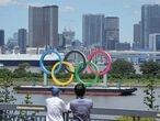 18 July 2021, Japan, Tokyo: Two people look at an Olympic rings monument on a raft in Tokyo Bay in front of the Odaiba district. Tokyo 2020 Olympic Games will be held from 23 July to 8 August 2021. Photo: Michael Kappeler/dpa 18/07/2021 ONLY FOR USE IN SPAIN
