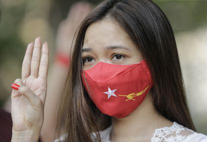 Manifestante com máscara do partido de Aung San Suu Kyi, no protesto deste sábado contra a junta militar em Yangon.