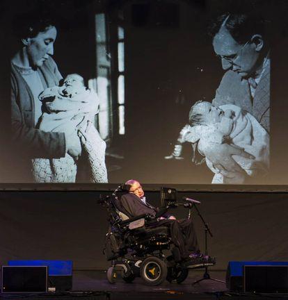Stephen Hawking, diante de duas fotos com sua mãe e seu pai.