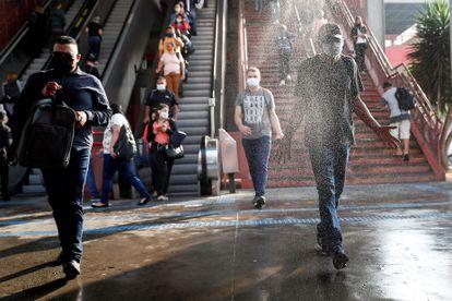 Usuários passam por zona de desinfecção ao sair de uma estação de metrô na cidade de Osasco, em São Paulo.