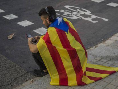 Um jovem sentado com uma bandeira da Catalunha em Barcelona nesta quinta.