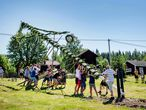 People erect a maypole for midsummer celebrations in Sahl near Leksand, Sweden, on June 19, 2020. - In the small village of Sahl in Dalarna, midsummer is celebrated to a lesser extent and the elderly in the village stay at home or keep a distance due to the novel coronavirus / COVID-19 pandemic. (Photo by Ulf PALM / TT News Agency / AFP) / Sweden OUT