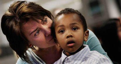 Uma mulher chora depois de concedida a cidadania norte-americana a seu filho adotivo etíope.