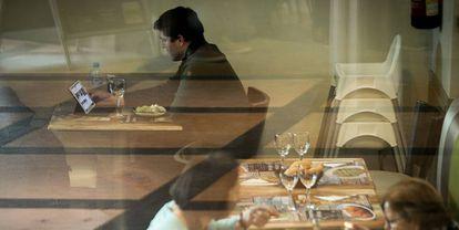 Um homem com seu tablet em um restaurante de Barcelona.