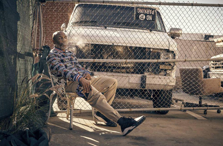 Mike Tyson descansa no quintal de seus vizinhos com uma jaqueta 'bomber', calça Dolce & Gabbana e tênis Adidas.