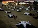 Nurses wearing protective face masks lie on the ground with signs bearing the names of healthcare professionals who died from the coronavirus disease (COVID-19) during a protest amid the COVID-19 outbreak in Brasilia, Brazil May 12, 2020. REUTERS/Adriano Machado