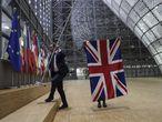 Dos funcionarios retiran la bandera de Reino Unido del interior del Consejo Europeo de Bruselas.