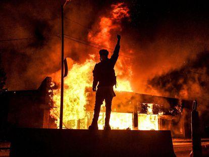 Um homem observa o fogo de um edifício em Minneapolis, na sexta-feira.