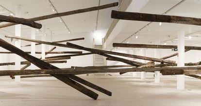 A obra 'sala de espera' (2013), feita com postes de madeira, de Carlito Carvalhosa, exposta no MAC-USP.