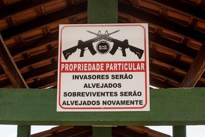 Uma placa no clube de tiro adverte que os invasores serão alvejados e os sobreviventes também.
