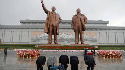 Cidadãos norte-coreanos prestam homenagem diante das estátuas de Kim Il-sung e Kim Jong-Il em Pyongyang.