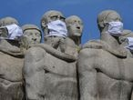 Statues of the Monumento das Bandeiras wear face masks in Sao Paulo, Brazil, on May 12, 2020, during the novel coronavirus COVID-19 pandemic. - Brazil has emerged as the epicenter of the pandemic in Latin America, with 11,519 deaths so far. (Photo by NELSON ALMEIDA / AFP)