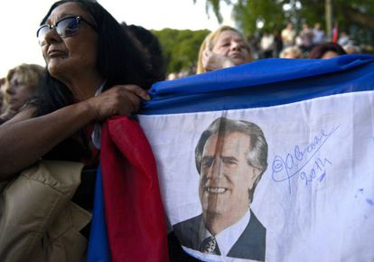 Uma mulher segura uma bandeira com a imagem de Vázquez.