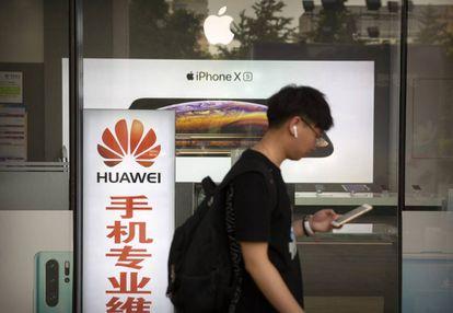 Homem caminha ao lado de uma loja com anúncios da Huawei e da Apple, em Pequim, na sexta-feira.