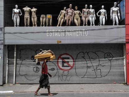Morador de rua caminha em via comercial esvaziada devido a quarentena no centro de São Paulo.