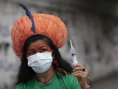 Militante indígena Tereza Arapium segura vacina durante protesto pelo Dia da Mulher, no Rio.