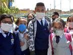 Colombian students pose for a picture wearing face masks made of recyclable and biodegradable materials, as a form of protest against the shortage of face masks in pharmacies, in order to prevent the spread of the COVID-19 virus, at Julio Cesar Turbay school, in Soacha, Colombia, on March 11, 2020. - The World Health Organisation (WHO) declared the Coronavirus a pandemic with 118,000 cases in about 120 countries, and 4000 deaths. (Photo by Raul ARBOLEDA / AFP)
