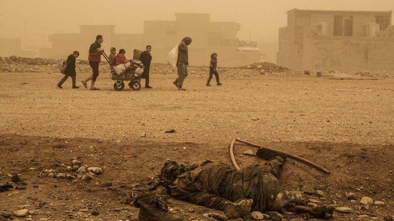 Civis passam por um corpo em Palmira, no início de dezembro.