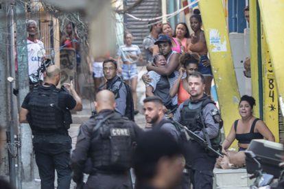 Moradores do Jacarezinho observam agentes da Polícia Civil que participavam da operação que terminou com a morte de 28 pessoas, no dia 6 de maio.