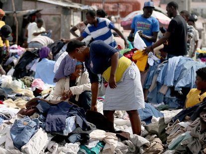Haitianos compram roupa em um mercado de rua.