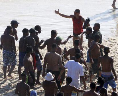 Ladrão e preso na praia e banhistas tentam resgatá-lo.