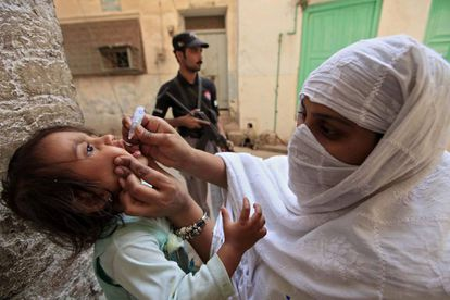 Mulher vacina menina contra a pólio em Peshawar (Paquistão).