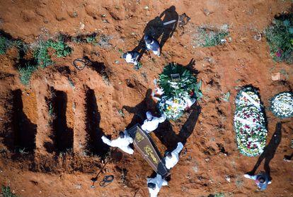 Trabalhadores do cemitério da Vila Formosa, em São Paulo, carregam um caixão nesta quarta-feira, 24 de março.
