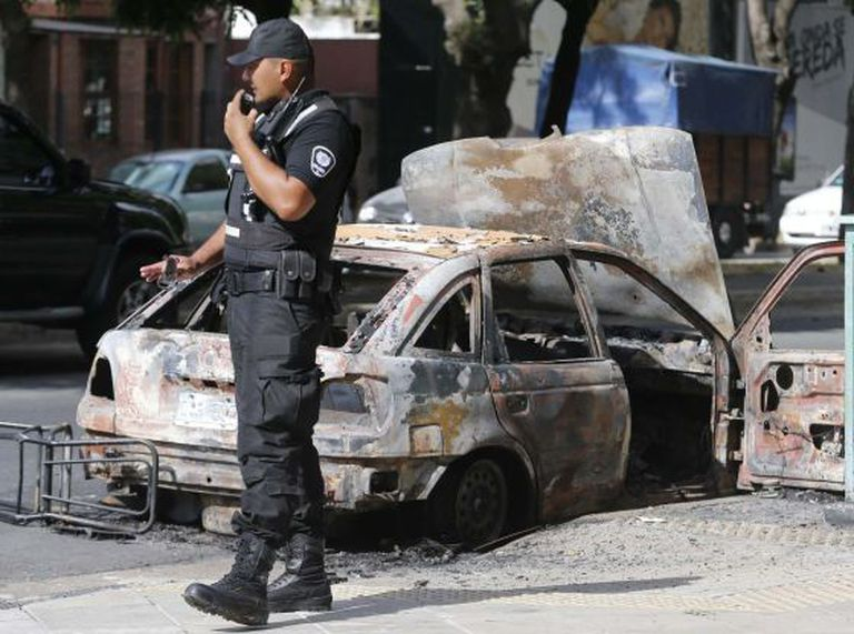 Um policial ao lado de um carro queimado por vândalos.