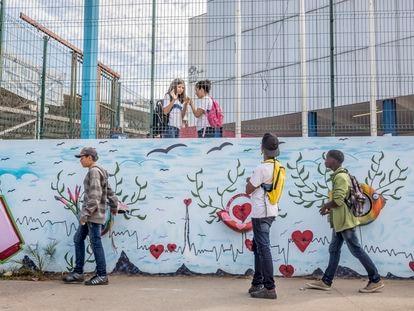 Os corações dissimulam os buracos de bala do muro de uma escola.