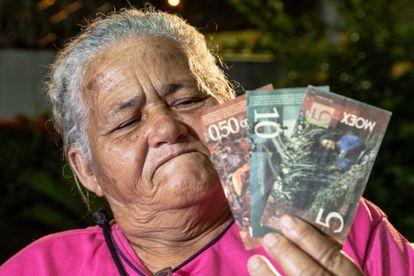 A pescadora Maria Conceição Cardoso mostra a moeda social da Resex de Canavieiras, na Bahia.