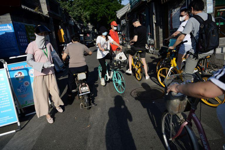Funcionária municipal verifica a temperatura de várias pessoas em uma rua de Pequim.
