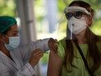 A woman receives a dose of the AstraZeneca COVID-19 vaccine, at a vaccination site set up at the Federal University in Rio de Janeiro, Brazil, Wednesday, June 2, 2021. (AP Photo/Silvia Izquierdo)