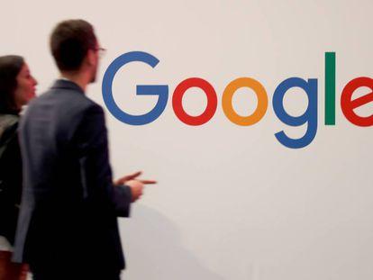 Duas pessoas passam junto ao logotipo do Google em Paris.
