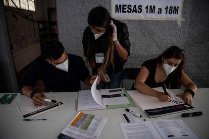 Membros do Serviço Eleitoral chileno preparam um ponto de votação em Santiago, horas antes do início do plebiscito deste domingo.