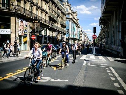 Parisienses percorrem a Rue de Rivoli de bicicleta.