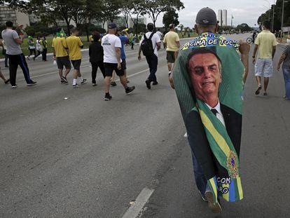 Manifestante carrega bandeira com imagem do presidente Jair Bolsonaro durante caravana em seu apoio em Brasília, no Primeiro de Maio.