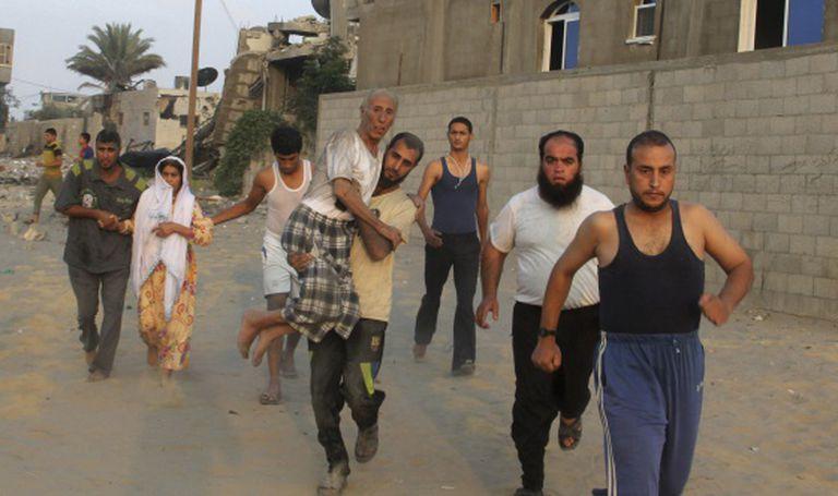 Moradores correm em busca de refúgio na Faixa de Gaza. / Hatem Ali (AFP)