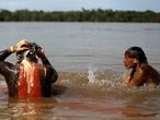 Indigenous men of the Xavantes tribe bathe in Xingu River during a four-day pow wow in Piaracu village, in Xingu Indigenous Park, near Sao Jose do Xingu, Mato Grosso state, Brazil, January 16, 2020. REUTERS/Ricardo Moraes