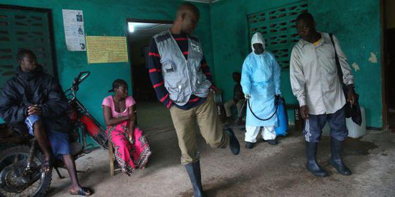 Médicos da Libéria desinfeta o calçado de pessoas que saem de um centro de isolamento.