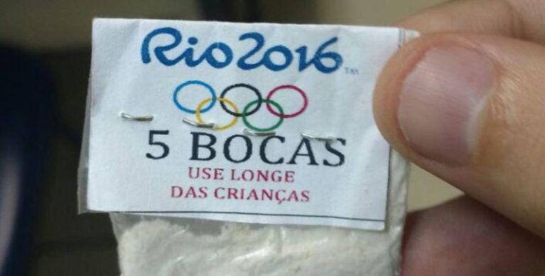 Envelope plástico de cocaína com o símbolo dos Jogos e a advertência.
