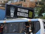 "Passengers travel on a crowded public bus past a banner against Brazil's President Jair Bolsonaro and his policies on the coronavirus disease (COVID-19) pandemic, in Rio de Janeiro, Brazil April 6, 2021. The banner reads ""Bolsonaro your government is genocidal"". REUTERS/Ricardo Moraes"