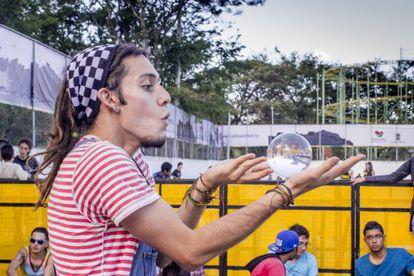 Um jovem faz malabarismo com uma esfera de cristal no Festival Altavoz de Medellín.