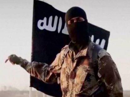 Homem encapuzado diante de uma bandeira do autoproclamado Estado Islâmico.