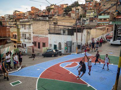 Crianças e jovens jogam basquete em uma quadra restaurada pelos moradores em um bairro de Caracas.