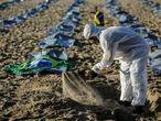 """GRAF5569 RIO DE JANEIRO (BRASIL), 30/04/21.- Un voluntario trabaja al amanecer para preparar el acto de la ONG Río de Paz en memoria de los más de 400.000 brasileños muertos por el Covid-19, este viernes en las arenas de la playa de Copacabana, en la zona sur de Río de Janeiro, Brasil. El país superó ayer la barrera de las 400.000 muertes por covid-19, con los hospitales aún en una situación """"crítica"""" y bajo el riesgo de sufrir una tercera ola de la pandemia, pese a la tímida desaceleración de las últimas dos semanas. EFE/Antonio Lacerda"""