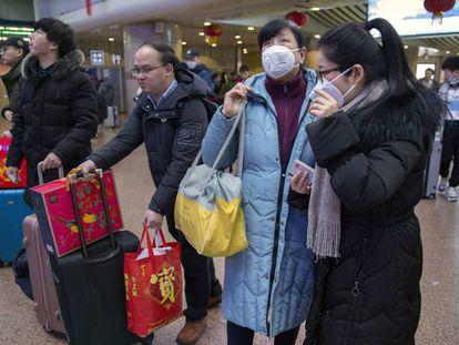 Um grupo de viajantes usa máscaras na Estação Ferroviária Oeste de Pequim nesta terça-feira.