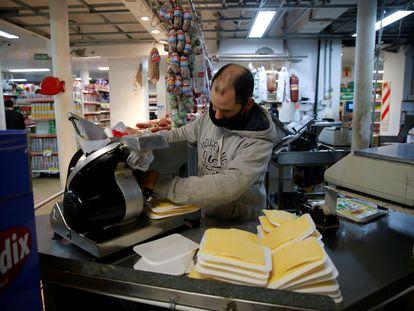 Funcionário de um supermercado empacota queijos na cidade de Buenos Aires.