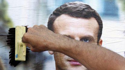 Simpatizante prega um cartaz do candidato Emmanuel Macron na quarta-feira em Bayonne.