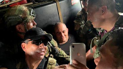 Otoniel, no centro, sorri para uma foto com militares colombianos dentro de um helicóptero após ser capturado.